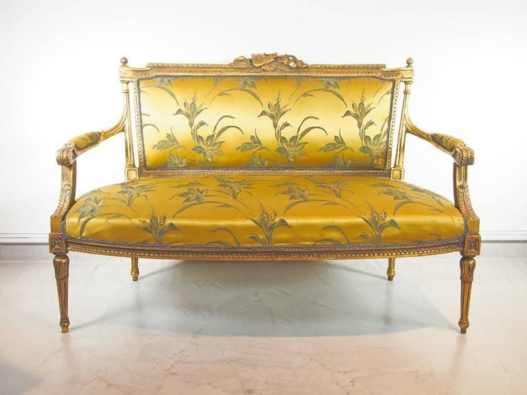 Beautiful giltwood sofa covered with golden silk fabric in the Louis XVI style. Slightly distressed wood richly carved with foliage and music emblems. Fluted tapered leg, padded seat, back and arms.