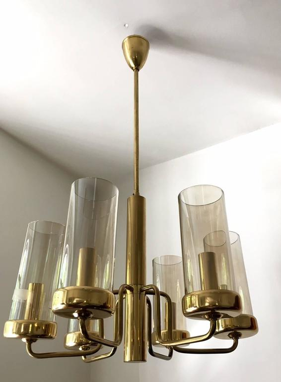 Beautiful brass ceiling lamp with six light arms. Cylindrical slightly tinted glass globes. One glass cylinder with a crack. In the style of Hans-Agne Jakobsson.