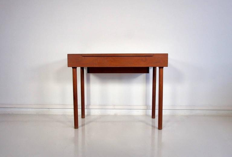 Mid-century Danish teak desk and dressing table with flip up top with brass fitting, mounted with mirror. Interior with storage room and movable tray.   Measures: Height 71 cm, height with mirror approximately 113 cm, width 90 cm, depth 51 cm.