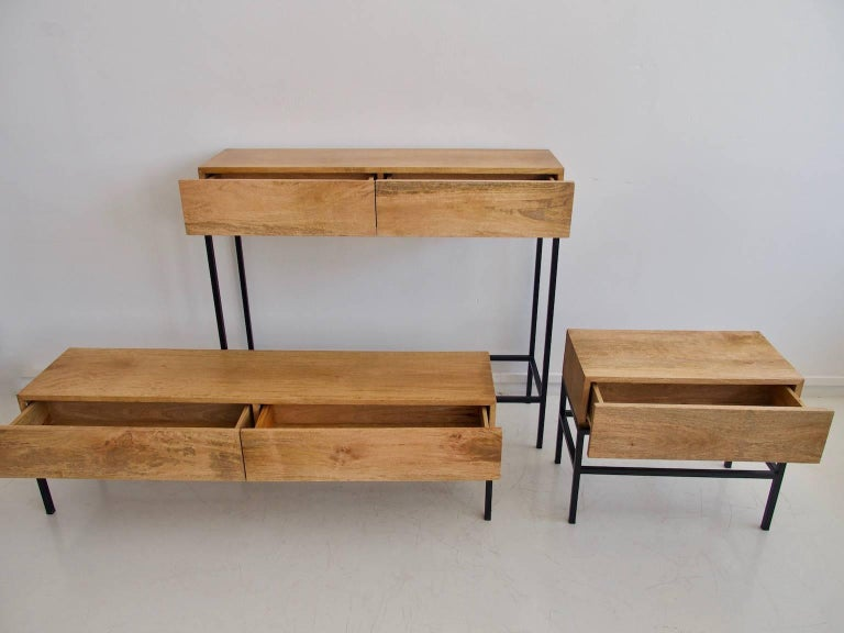 Set of two console tables and a TV bench. Respectively with one drawer and two drawers. Mango wood, black-varnished steel base. Measure: High console H 109 x L 120 x D 35 cm Medium console H 56 x L 65 x D 35cm Low console H 46 x L 150 x D 35cm.