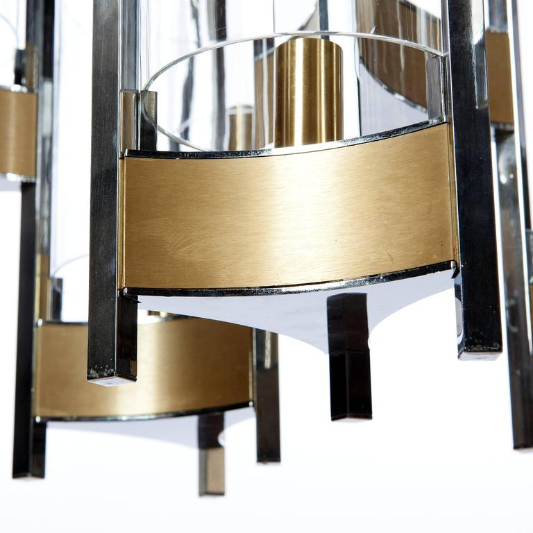 Gaetano Sciolari monumental chrome and brushed brass two-tier nine-light chandelier with cylindrical glass shades, 1960s. Please note, we have sconces in the same style. Please do not hesitate to ask for more information.