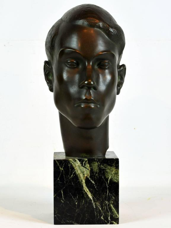 Standing almost 18 inches tall and superbly modeled in the modernist/art deco tradition of the early 20th century this bronze head on a green marble cube base catches the very essence of the sitter's personality in a sculptural form of great and