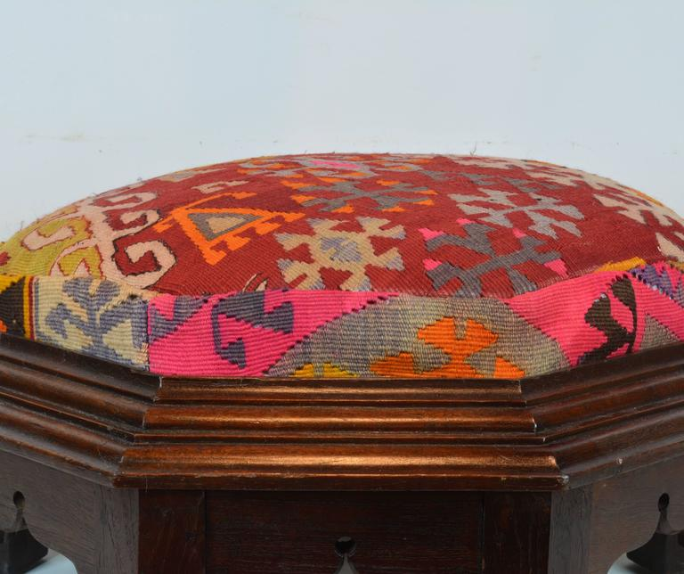Standing on eight legs flanking carved oriental openings this ottoman features a richly moulded frame surrounding the upholstered seat covered with colorful geometrical pattern Kilim rug.