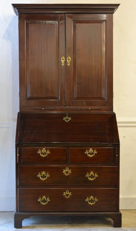A charming secretary bookcase of rather small proportions. The upper part with two doors opening up to a shelved interior, the lower fall front desk fitted with small compartments and drawers with original brasses above two short and two long