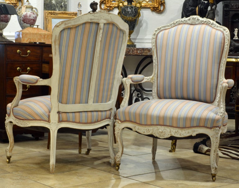 Of generous proportions this pair of 'fauteuil' chairs feature delicate carvings of the Louis XV period executed in relief along the crest and throughout the apron brought into character by the distressed whitish paint. The front legs ending in