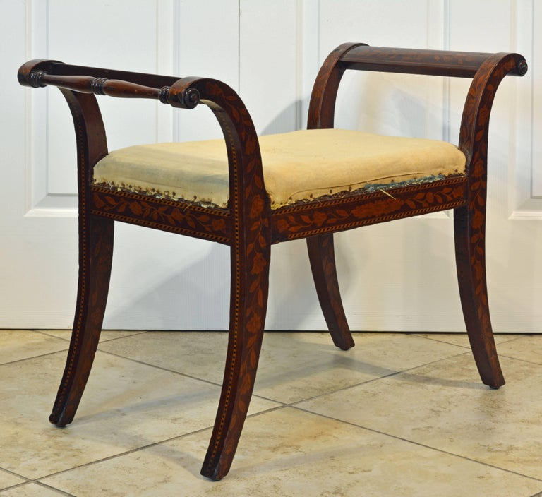 With beautiful overall inlay of flowers and leaf work this elegant mahogany bench features the neoclassical splayed legs and curved arm rests. It is ready for the final upholstery fabric.