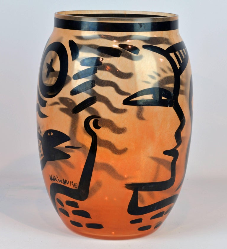 Ulrica Hydman-Vallien is known for her bold approach to figurative art and for her use of archetypal motifs in this case the Adam and Eve theme. Standing 13.5 inches tall this handblown and artist painted amber colored vase by Swedish Kosta Boda has