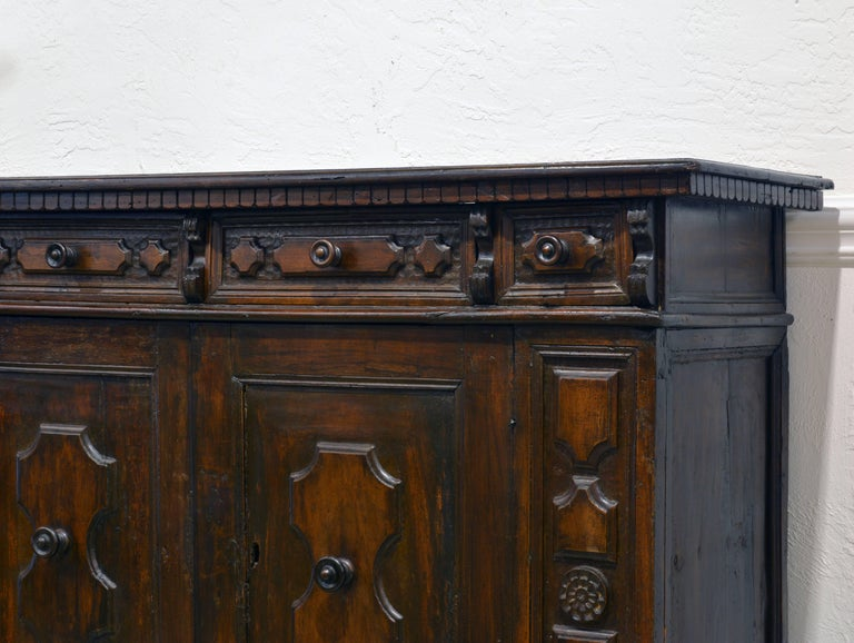 This carved buffet is a fine example of Italian Provincial Baroque featuring a one plank top of beautiful patina above four carved frieze drawers and two doors flanked by carved panels.