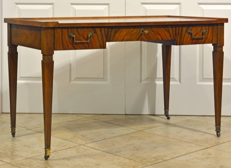 This Classic desk of versatile dimensions features a beautifully figured walnut writing surface surrounded by a gallery lip on three sides above three frieze drawers with solid brass handles resting on square tapering legs and brass casters. In