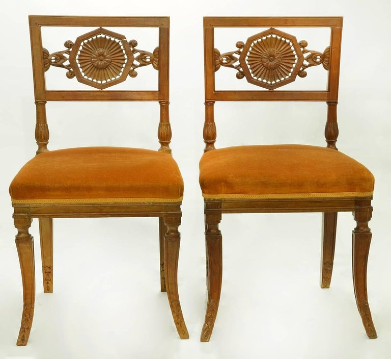 A pair of rare Italian neoclassical side chairs with wonderfully carved reticulated foliage splats centring sunbursts, resting on classical splayed sabre legs. These chairs date to the early 19th century.