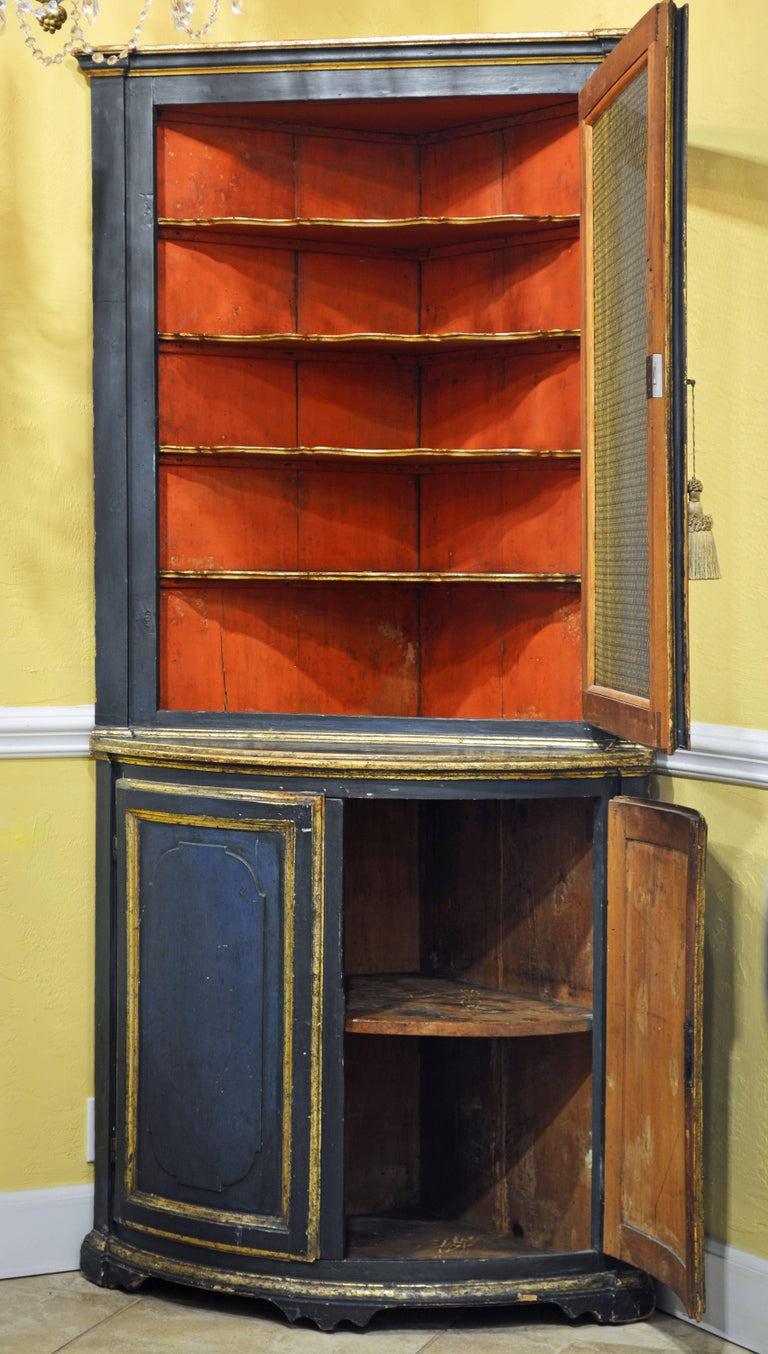 The combination of the subtle blue color and gilt trim makes this corner cabinet especially attractive. The two upper mesh doors open up to a Venetian red interior with shaped gilt trimmed shelves, the lower carved panel doors encloses a one shelf