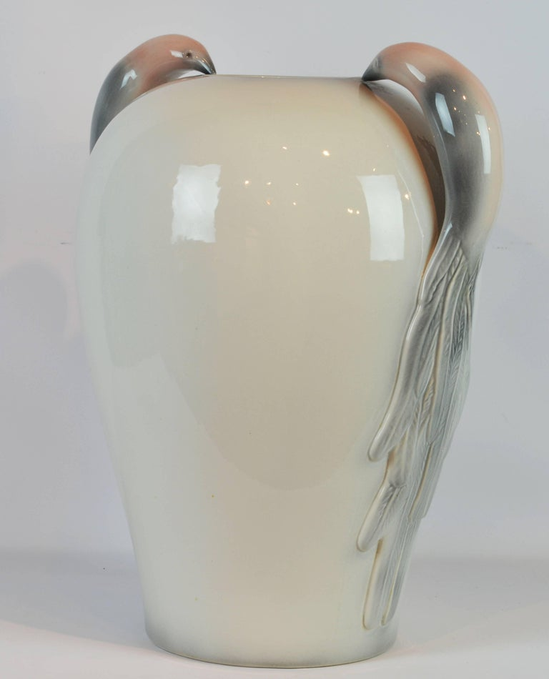 Standing 24 inches tall this elegant and unique vase of subtle color features a stunning pair of handles in the shape of birds of paradise stylized in the Art Deco manner.
