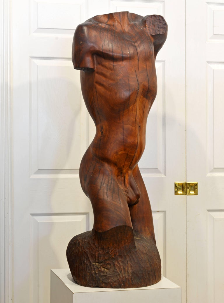 Standing 47 inches tall this statue is carved out of a hardwood tree trunk and combines naturally organic lines with the artist strong intentions. The statue offers new surprising perspectives from all sides complimented by the warm wood tones and