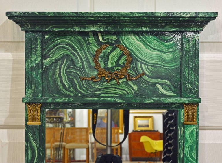 This malachite painted mirror features a neoclassical form with a moulded corniche and gilt bronze mounted top panel above the mirror flanked by bronze crowned pilasters.