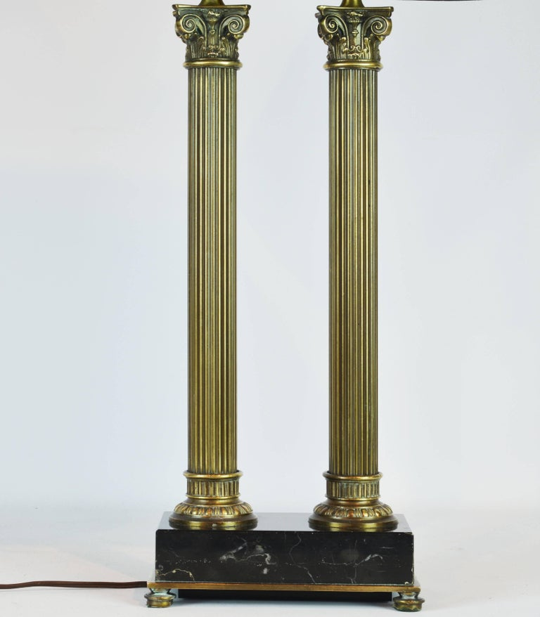This French table lamp in the neoclassical architectural style features a bronze edged marquina marble base raised on bronze feet supporting two bronze columns surmounted by well detailed corinthian capitals. Measurements below are including the