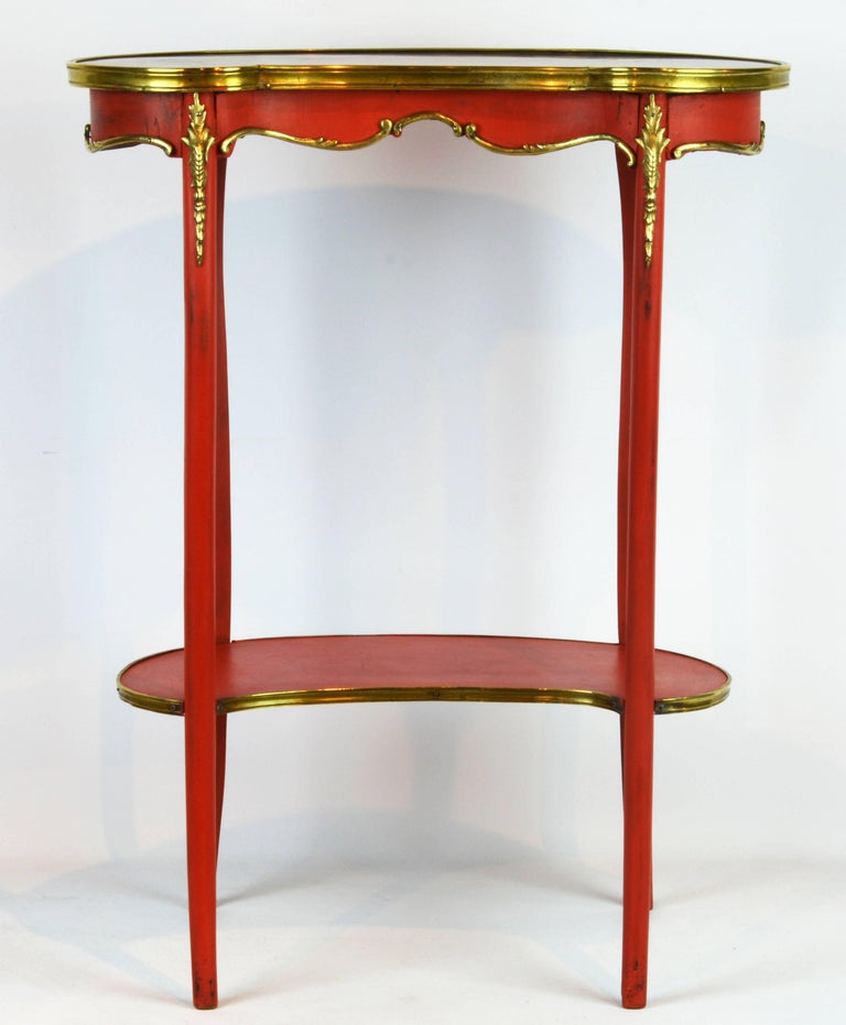 This charming late 19th century table features a kidney shaped and bronze edged marble top above a scalloped bronze-mounted frieze raised on for round slender cabriole legs joined by a lower bronze edged tier shelf.