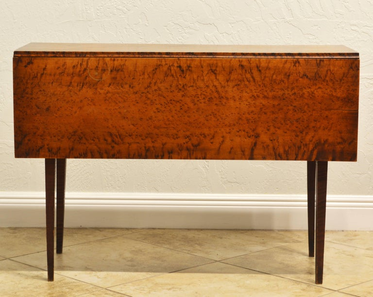 This fine New England tiger maple with bird's-eyes drop-leaf table dating to the late 18th or early 19th century is about as good as they get. The almost square top resting of a frieze with swing out leaf brackets on four square tapering tiger maple
