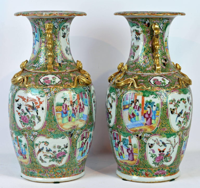 This fine 19th century pair of rose medallion vases adorned with high relief gilt lizards and animal handles feature cartouches depicting family life, flowers and birds on a green and pink enameled ground.