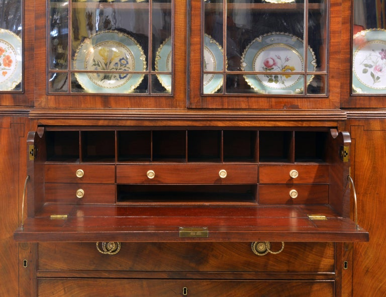 This stately secretary bookcase of great proportions features a central drawer which upon pull out opens up to an interior fitted with smaller drawers and open compartments above a burgundy red and gilt tooled leather writing surface. The four