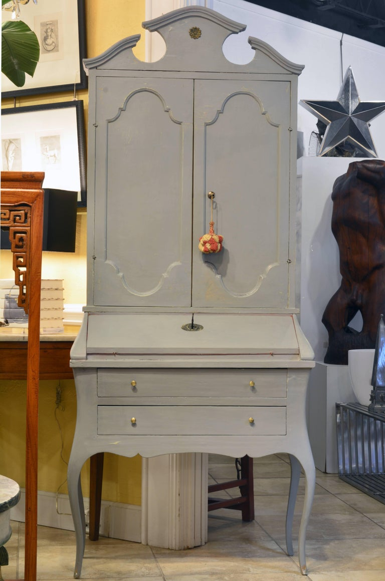 This fetching two part grey painted secretary desk features an upper cabinet crowned by shaped pediments above two-panel doors opening up to a shelved and paper lined interior. The lower part offers a slant front opening up to a Venetian red