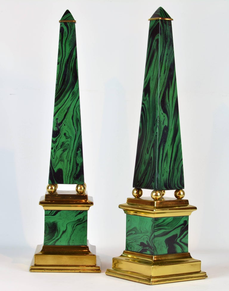 Standing almost 22 inches tall this beautifully crafted pair of obelisk models in the neoclassical style feature faux malachite enameled surfaces intersected by polished brass elements on the top, between shaft and bases and as stepped foot bases.