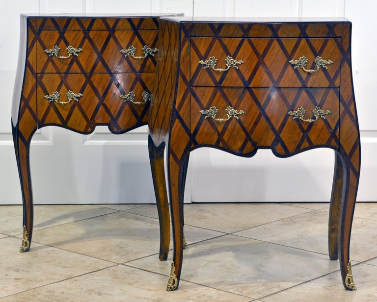 The parquetry lattice or diamond strap work continuing on the caddy-style tops make these commodes uniquely attractive. The design is in the Louis XV bombe taste with two drawers above shaped aprons resting on cabriole legs ending in gilt bronze