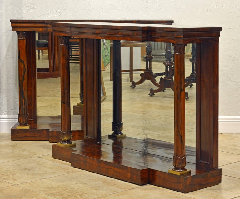 This rare pair of early 19th century Regency breakfront console tables feature string inlaid polished tops above profiled friezes resting on double columns with carved capitals and bases flanking mirrored back panels and standing on a plinth bases.