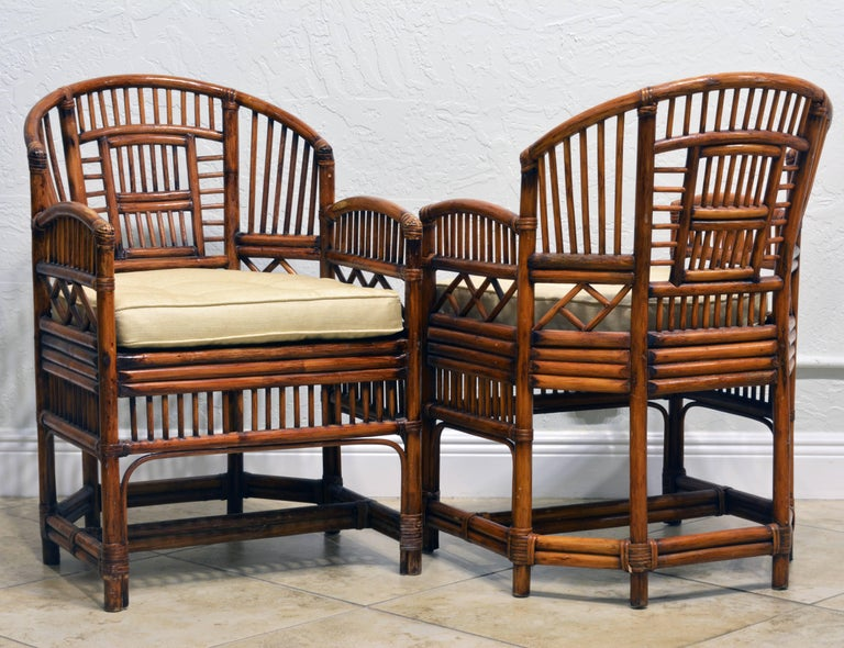 Rising on six legs these intricately crafted iconic chairs with cane seats feature bamboo frames and Chinese themed bamboo open work inspired by Chippendale design. The chairs come with new off-white silk cushions in pristine condition.