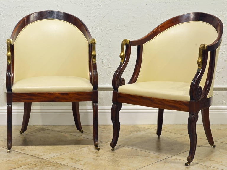 These chairs from the second half of the 19th century feature elegant curved backs and beautiful open arm rests accented by brass swan figures. The carved and scrolled front legs as well as the classical saber back legs rest on small brass castors.