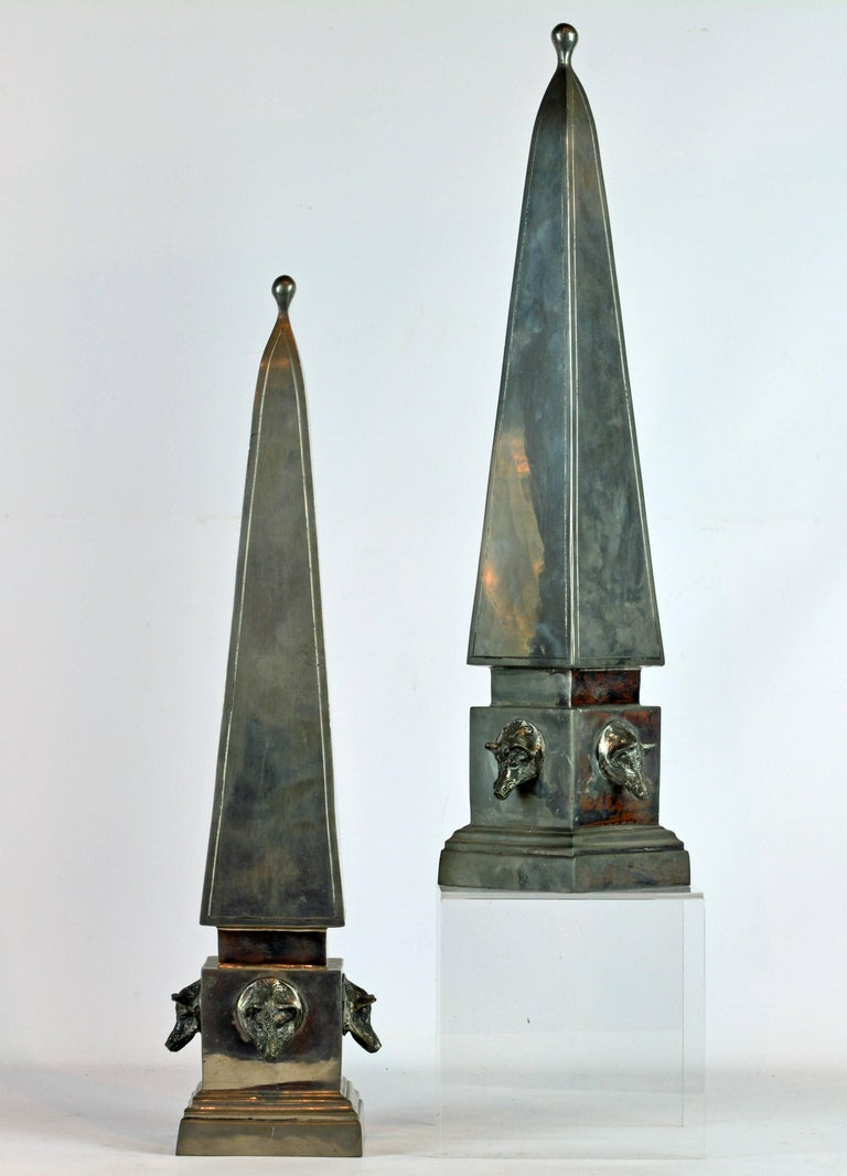 Standing 20 inches tall these unique hunting themed pewter obelisks model in the neoclassical style feature beautiful craftsmanship and detail. Each base is mounted with four boar's heads adding a sculptural quality to their appearance. The obelisks