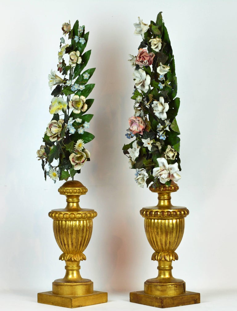 A lovely pair of table decorations with hand carved gilt wood urns supporting tall arrangements of polychrome painted tole flowers and leaves. A closer look at the photos shows the multitude of different flowers combined. 19th Century