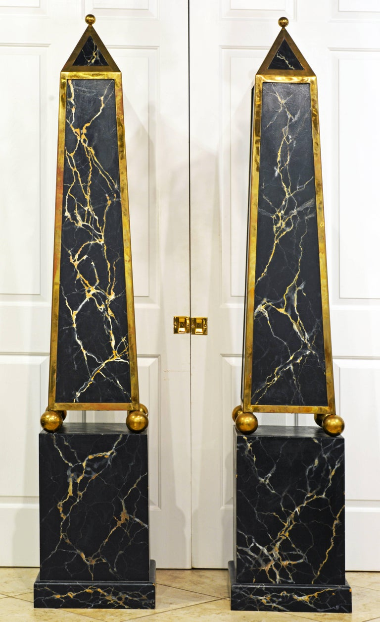 Standing an impressive 81 inches tall these magnificent obelisk models feature upper solid brass mounted and marble painted sections surmounted by finials and resting on solid brass spheres on square likewise marble painted bases. Each obelisks has