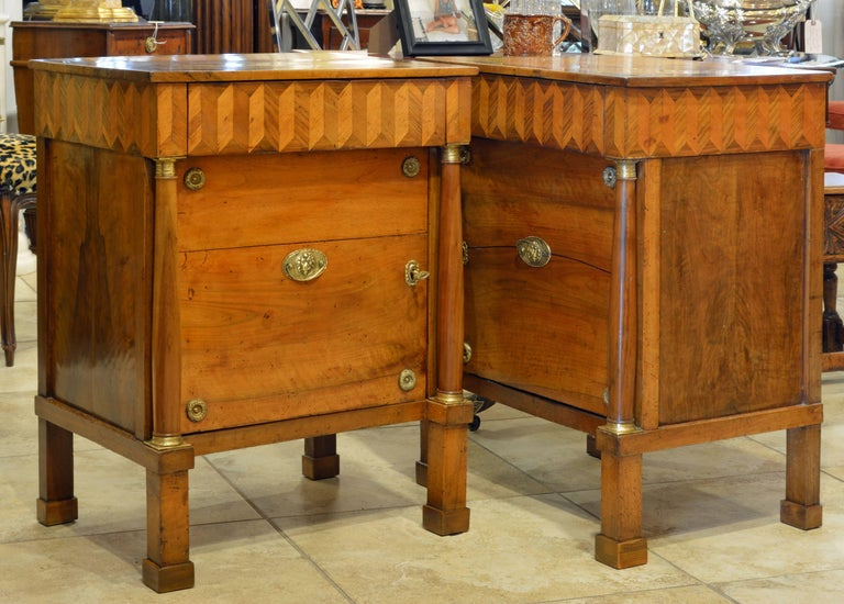 This lovely pair of Italian neoclassical commodes feature a fetching arrow parquetry frieze with one drawer above a bronze accented door opening up to a one shelf interior and flanked by classical style columns with bronze mounted capitals and