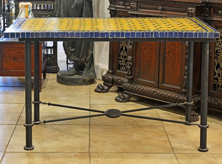 The yellow, blue and green colors of the Venetian style mosaic make this table very attractive both for indoor and outdoor use. Its iron frame is designed in the classical Pompeian style with round legs spearheaded stretchers united by a circular