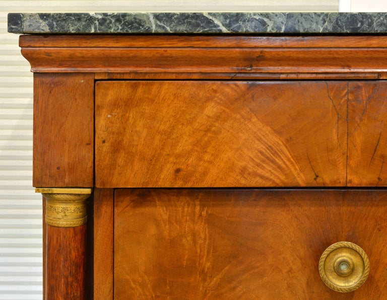 Of refined Empire style and with beautifully figured veneers this commode stands out as a fine representative of the Napoleonic era. It features a newer marble top above three long drawers flanked by gilt bronze-mounted columns supported by square