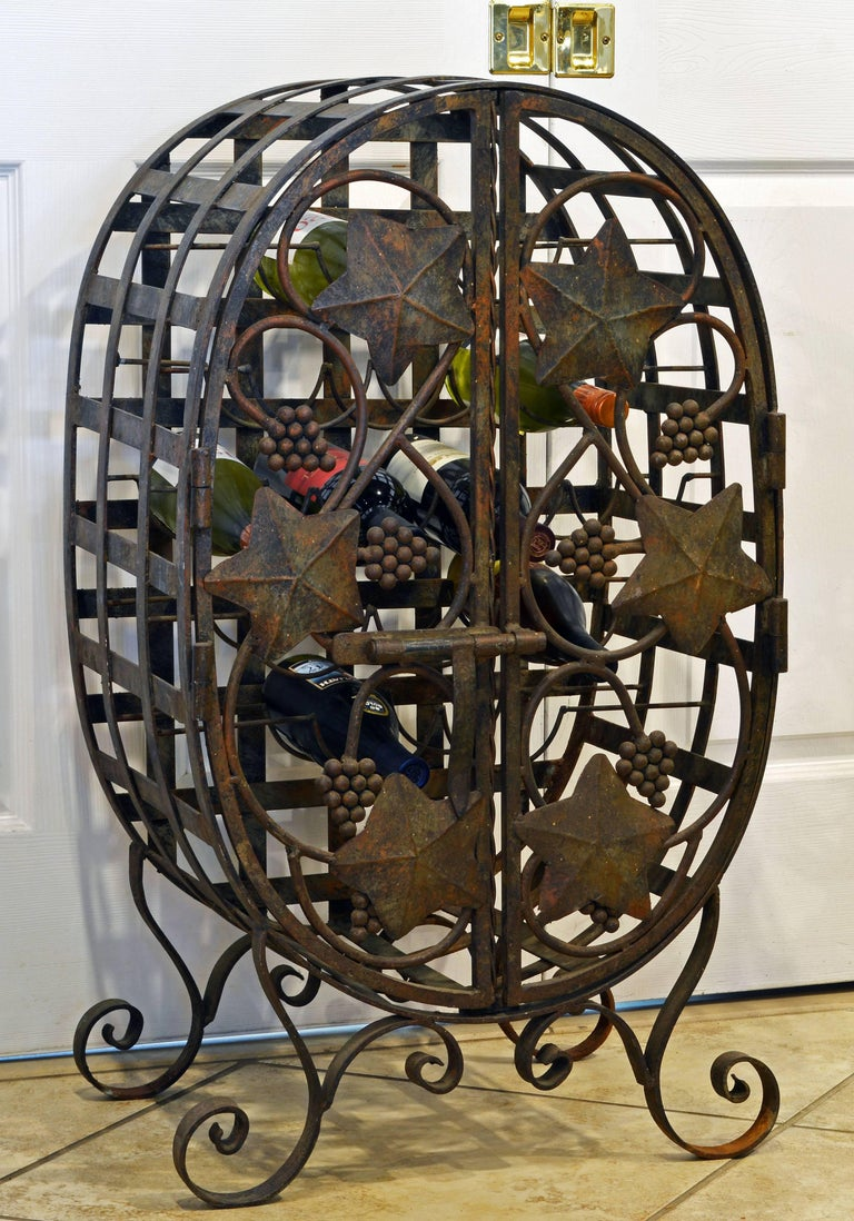 Designed in the shape of a wine barrel and decorated with grapes and grape leaves this charming wine jail or cage standing on scrolled legs can sit either on the floor or on a table. The well-made rustic doors open up to an interior with bottle