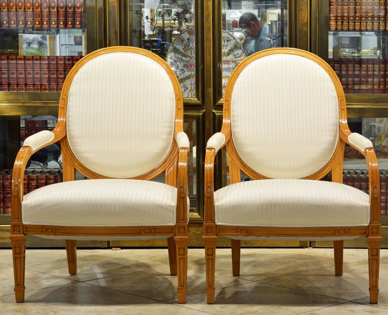 These satinwood oval back armchairs are fashioned in the Louis XVI style with detail and carved motifs reflecting the Art Deco era. Delicately covered by white structured fabric complimenting the blonde wood the gently restored chairs make an