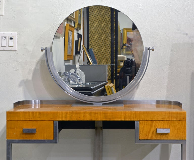 Designed with an Art Deco style stainless steel frame supporting a tiger maple veneered body of top and drawers rounded to the back this desk is a typical representative of 'machine age' furniture. The combination of wood and steel is indicative of