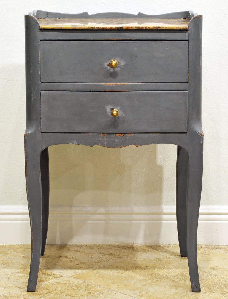 This commode likely dates to the end of the 19th century or the early 20th century. It features a polychrome marble top surrounded on three sides by a scalloped edge above two drawers and resting on elegant cabriole legs. At a later time painted