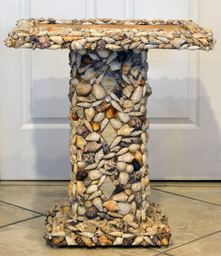 A unique sea shell and mirror encrusted pedestal accent table with the top of woven raffia. Well constructed of an inner core of particle board and quite heavy. Ideal for that beach ambiance or the room with maritime connotations.