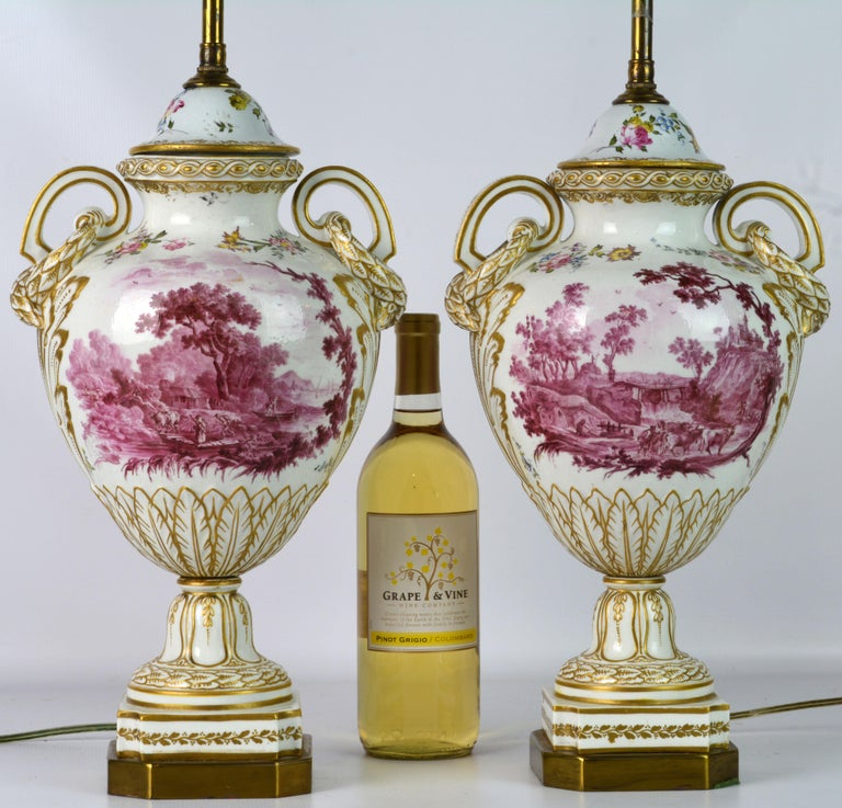 These large French old Paris porcelain lamps feature purple 'puce camaieu' landscape paintings on both sides set on gilt decorated white ground. The form is typical for the Louis XVI style and features elegant laurel draped scrolled handles. The