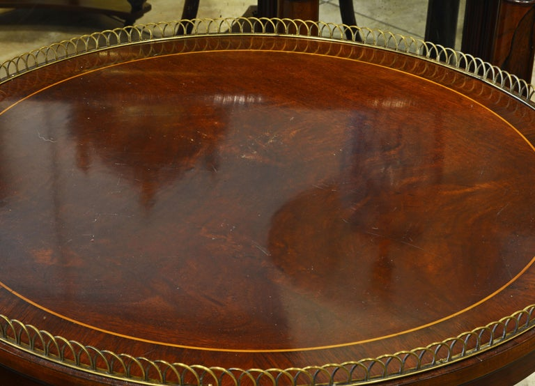 This fine pair of French Directoire style tables feature rosewood banded mahogany tops edged by circle segment bronze galleries and supported by three curved legs carved with scrolls united by a second tier gallery shelf and resting on a shaped