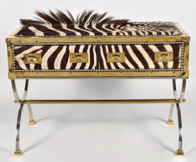 This eye-catching commode features a two drawer brass edged campaign style box or trunk covered with zebra skin on the front and top and with black leather on back and sides accented by steel nail head trim. It rests on a curule style finely