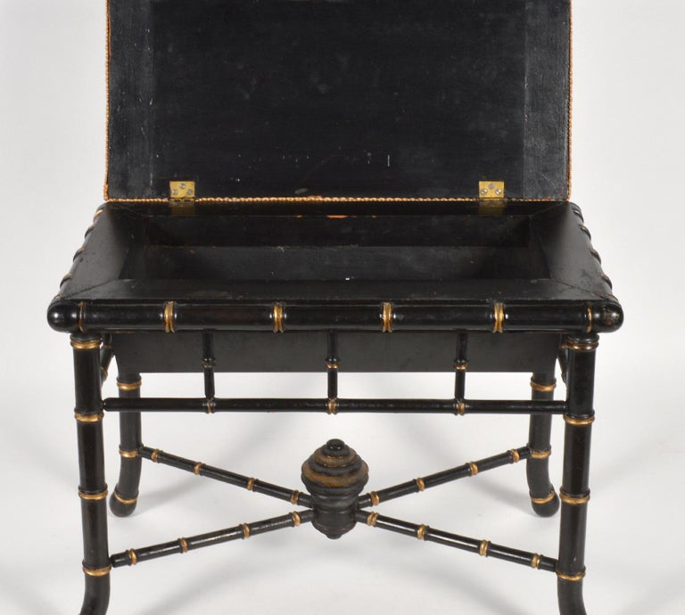 This elegant Regency style bench features an ebonized and gilt accented faux bamboo frame with four splayed legs united by a low x-stretcher centering a carved and turned ornament, 19th century. The upholstered seat opens up to an interior storage