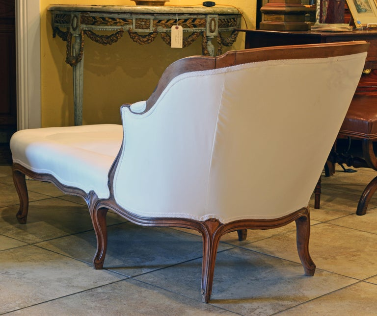 This elegant and comfortable French Provincial chaise longue features a delicately carved walnut frame resting on 6 carved cabriole legs. It has recently been reupholstered and covered with white fabric.