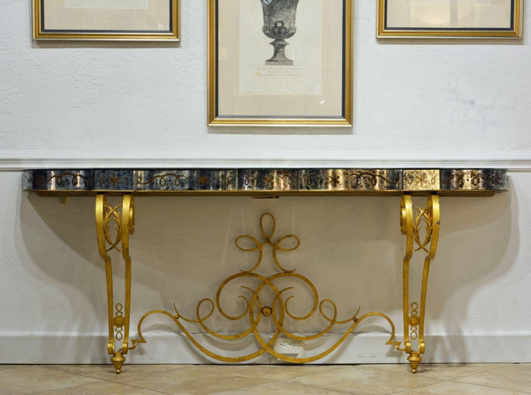 This superb and rare console table features an antiqued gilt inlaid mirrored top on a scrolled gilt iron frame in the manner of legendary French metal designer Raymond Subes (1893-1970). The top is shaped by serpentine and circular segments accented