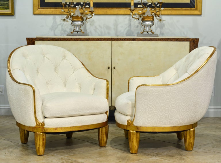 Gently restored to their original glory these wonderful lounge chairs or bergeres, attributed to the legendary furniture designer Maurice Dufrene, feature reeded conical legs typical of Dufrene and a narrow gilded frame in an elegant curvature