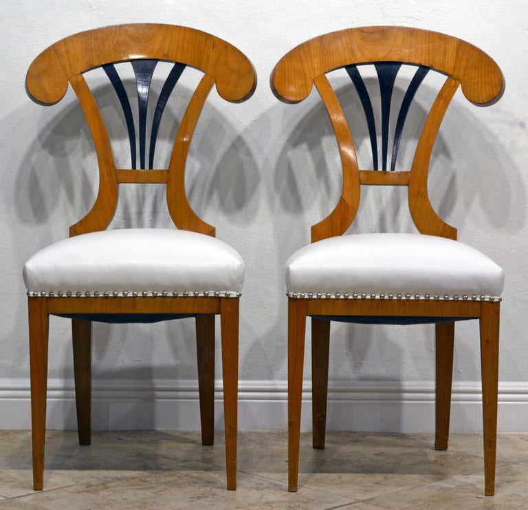 These Austrian salon or side chairs date to the mid 19th century and are great examples of the Biedermeier style. The focal point is the ebonized fan-shape splat surmounted by a boldly arched top-rail. The seats are recently reupholstered and