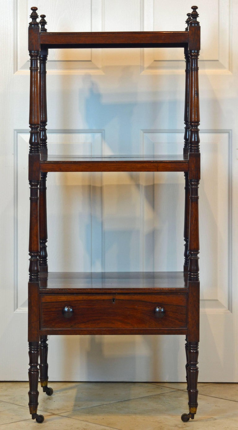 This late Georgian rosewood étagère features three shelves raised on elegantly turned and carved supports surmounted by finials and ending in brass casters. Under the lower shelf a long drawer with turned knobs.
