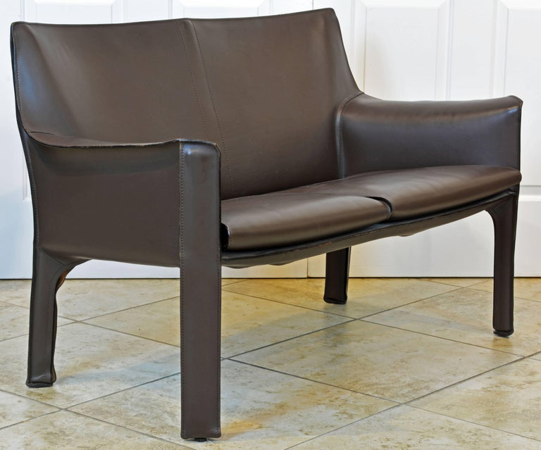 This iconic Mario Bellini leather loveseat by Cassina is constructed with a steel frame totally covered in 1st grade mocha tanned leather in good condition. The love seat is branded as shown on photos. Please note that we have a pair of cab lounge